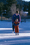 A mother helps her son ice skate on a frozen lake, Rocky Mountains, CO
