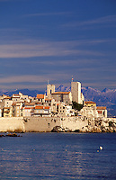 France. Provence. Cote d'Azur.  View of Antibes old town across the bay with the foothills of the Alps in the background.