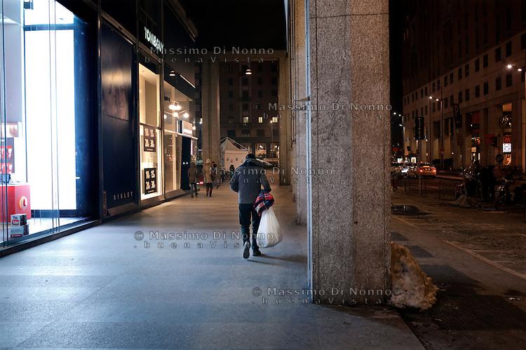 Milano: un senzatetto cammina in centro di Milano ddopo aver preso una coperta e dei viveri.
