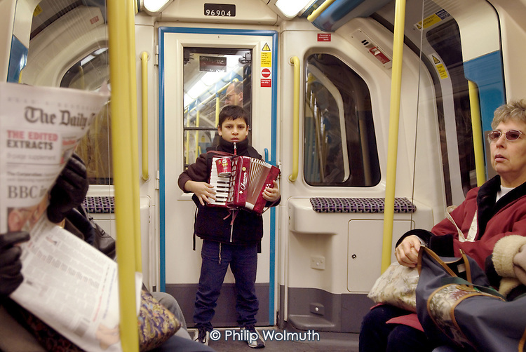 A young Roma boy busks with an accordion on a London underground train.