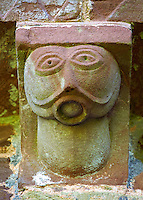 Norman Romanesque exterior corbel no 49  - sculpture of  an alien like chinless bald headed figure. Its perfectly round mouth is filled with a ball like object and may be a moral warning about talking too much. The Norman Romanesque Church of St Mary and St David, Kilpeck Herefordshire, England. Built around 1140