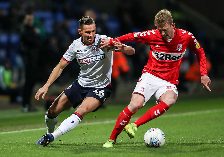 Bolton Wanderers' Pawel Olkowski competing with Middlesbrough's George Saville <br /> <br /> Photographer Andrew Kearns/CameraSport<br /> <br /> The EFL Sky Bet Championship - Bolton Wanderers v Middlesbrough -Tuesday 9th April 2019 - University of Bolton Stadium - Bolton<br /> <br /> World Copyright © 2019 CameraSport. All rights reserved. 43 Linden Ave. Countesthorpe. Leicester. England. LE8 5PG - Tel: +44 (0) 116 277 4147 - admin@camerasport.com - www.camerasport.com