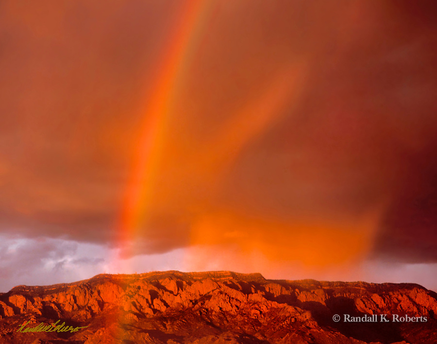 A rainbow and storm clouds paint the sky over the Sandia Mountains in Albuquerque, New Mexico