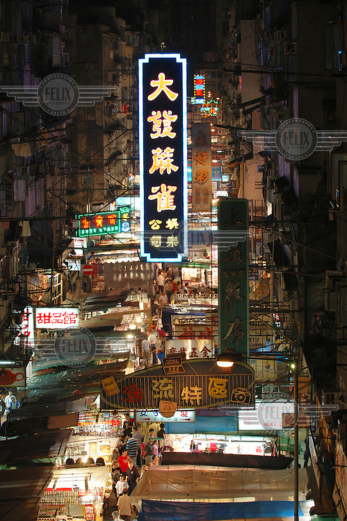 Stalls and neon signs at Temple Street night market in the densely populated Kowloon.
