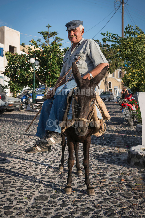 A man rides side-saddle on his donkey, Fira, Santorini, Greece
