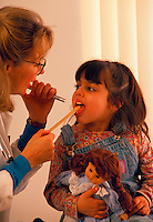 Doctor checking inside the mouth of her young patient using a tongue depressor during a check-up.