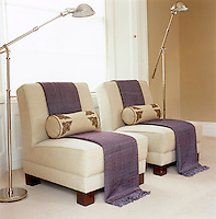 On a pair of plain oatmeal armchairs In the living room violet bolsters and runners are used to ring the changes