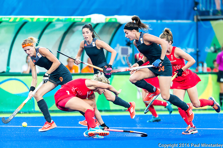 Eva de Goede #24 of Netherlands leaps to avoid a collision after passing the ball to \Carlien Dirkse van den Heuvel #9 of Netherlands during Netherlands vs Great Britain in the gold medal final at the Rio 2016 Olympics at the Olympic Hockey Centre in Rio de Janeiro, Brazil.