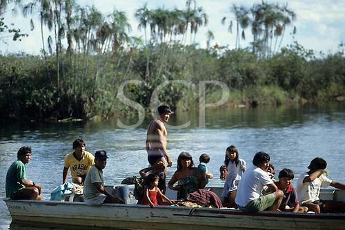 Xingu, Brazil. Posto Leonardo; group of Indian men, women and children in a boat.