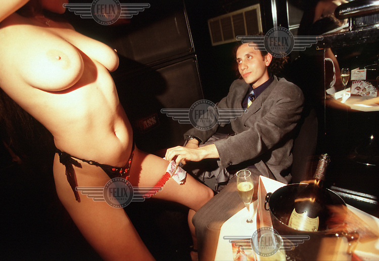 A client slips some money to one of the 'Angels' at the Stringfellow's lapdancing club.