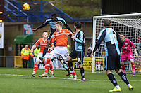 Aaron Pierre of Wycombe Wanderers clears the ball ahead of Joe Pigott of Luton Town during the Sky Bet League 2 match between Wycombe Wanderers and Luton Town at Adams Park, High Wycombe, England on 6 February 2016. Photo by David Horn.