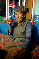 A woman sips butter tea from a wooden bowl in Junba Village, Tibet's only fishing village.