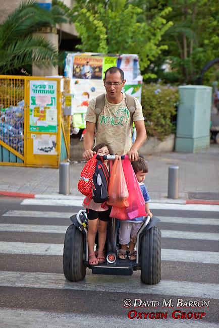 Man & Children On Segway Type Device
