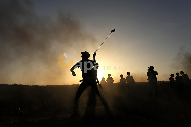 A masked Palestinian protester hurls a stone towards Israeli troops during clashes near a border fence between Israel and the Gaza Strip on October 14, 2015 east of Bureij in central Gaza. The outbreak of violence between Palestinians and Israeli forces in recent weeks has worsened in October, raising fears of a third intifada, or uprising. Photo by Ashraf Amra