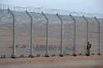 An Israeli soldier inspects Eritrean immigrants behind the newly-built fence in Israel-Egypt border, after they arrived a week earlier at the spot, crossed the old fence but got trapped by the new one. Israeli soldiers have been providing the group with water, but not allowing them into Israel.<br />