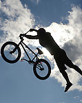 Stunt cyclist against clouds