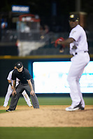 Third base umpire Scott Costello keeps an eye on Charlotte Knights relief pitcher Thyago Vieira (10) during the game against the Toledo Mud Hens at BB&T BallPark on April 23, 2019 in Charlotte, North Carolina. The Knights defeated the Mud Hens 11-9 in 10 innings. (Brian Westerholt/Four Seam Images)