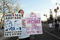 Mesa, Arizona. February 23, 2012 - As Republican candidates debated in the Mesa Arts Center, protesters including undocumented students, tea partiers, occupy movement members and Syrian president opponents, shouted slogans and held up signs and placards outside. In this photograph, a man holds signs against immigration enforcement by Maricopa County (Arizona) Sheriff Joe Arpaio and deportation policies of U.S. president Barack Obama. The man belongs to the immigrant and human rights Arizona-based group Puente Movement. Photo by Eduardo Barraza © 2012
