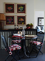 In the breakfast room, folding chairs by Ilaria Miani, with cushions in a Boussac stripe, surround a circa-1900 Thonet bentwood table; the still-life frescoes are by Anna Chiara Branca.
