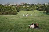 Young couple on Primrose Hill, overlooking highrise blocks in Docklands and the City of London.
