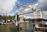 Historic boats and buildings in Wolwevershaven, Dordrecht, Netherlands with old industrial sign and crane.