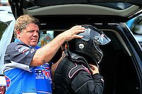 Aug. 2, 2014; Kent, WA, USA; Funny car driver Terry Haddock (left) helps dress wife NHRA top fuel dragster driver Jenna Haddock into her safety gear during qualifying for the Northwest Nationals at Pacific Raceways. Mandatory Credit: Mark J. Rebilas-