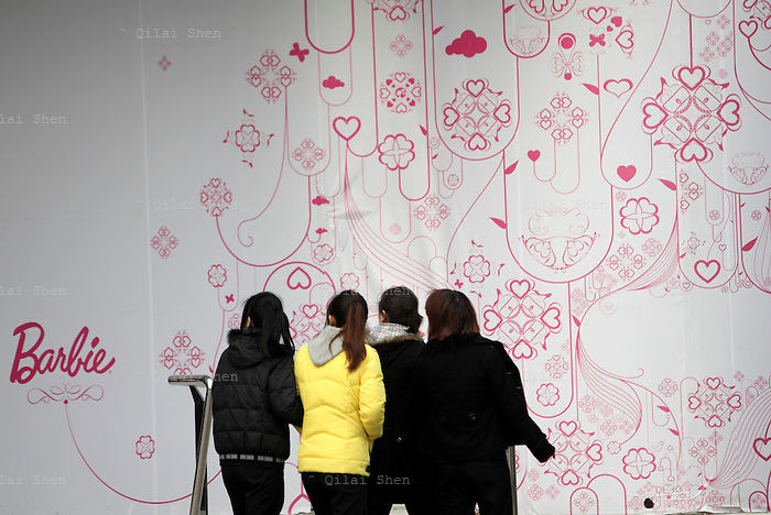 Pedestrians walk past the new Barbie Shanghai flagship store in Shanghai, China on 20 February 2009.  The Barbie store has become a hit in Shanghai as a place where doting mothers take their daughters, often the only child in the family, for a girls' day out.