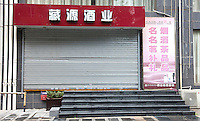 "A shop that collects authentic empty bottles of high end wine, Guangzhou, Guangdong Province, China, 18 July 2014. The Chinese sign above the shop reads in English, ""Hidden Source Liquor Industry"". Collected empty bottles are often recycled into the Chinese underground fake wine industry.<br /> <br /> PHOTO BY SINOPIX"