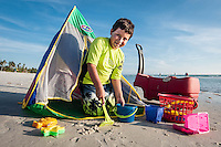 Matthew Moreira, 8, in rental pop-up beach tent and basket of toys at Twinkle, Twinkle Little Store, on beach near Naples Fishing Pier Gulf of Mexico, Naples, Florida, USA. Photo by Debi Pittman Wilkey/News-Press.com.