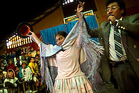 John Perales asks the crowd to support 18 year old wrestler Gloria Esperanza (fighting name), Esperanza Gomez (real name) before her first fight at the Multifuncional building. Esperanza is a Cholita, a wrestler of native Aymara descent. When Cholitas fight they wear traditional costume...