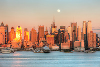 The waxing gibbous moon rises over the New York City skyline the day before the full moon, as the setting sun in the west reflects off the windows and facades of the Manhattan skyscrapers.