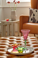 Coloured glassware pieces are displayed on an upholstered leather ottoman
