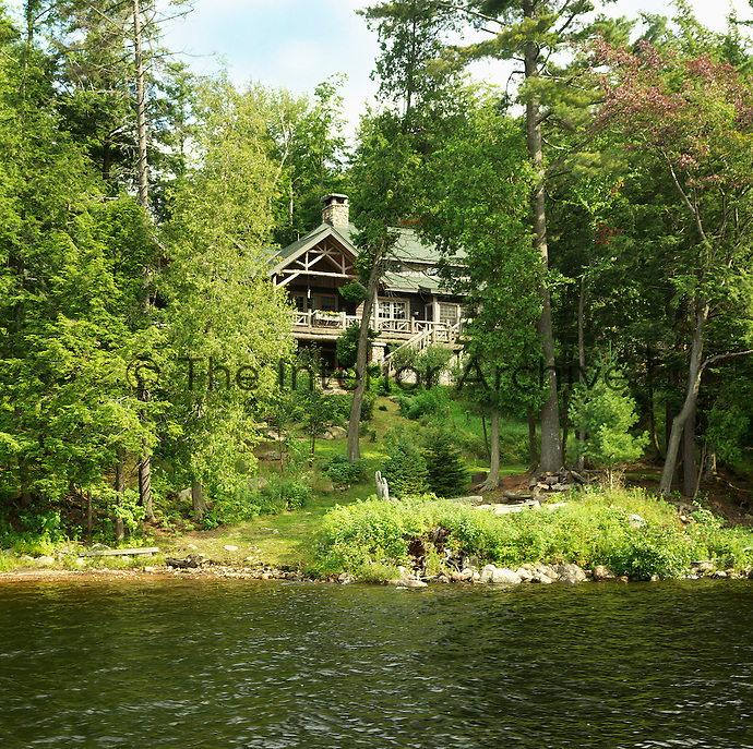 The log cabin is set amongst the trees beside a lake in the Adirondack mountains