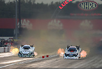Aug. 31, 2012; Claremont, IN, USA: NHRA funny car driver Mike Neff (left) races alongside Courtney Force during qualifying for the US Nationals at Lucas Oil Raceway. Mandatory Credit: Mark J. Rebilas-