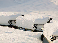 Snow heaps on benches in one of the town parks, in Tromso, Norway