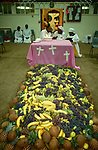 The Celestial Church of Christ. A baby naming ceremony.  Church members have just danced around the huge pile of fruit. The child is being held by a 'spirit medium', in the middle of the group, to her left a 'scribe' translates the 'spirit mediums' prophecies for the child, she is speaking in  tongues. The child's father records her message. The mother is considered 'unclean' and remains outside of the church hall in an anteroom with her other children.  1990s London UK