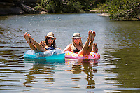Two attractive females lounge on inner tube floats at a swimming hole on the Bull Creek Greenbelt, Austin, Texas.
