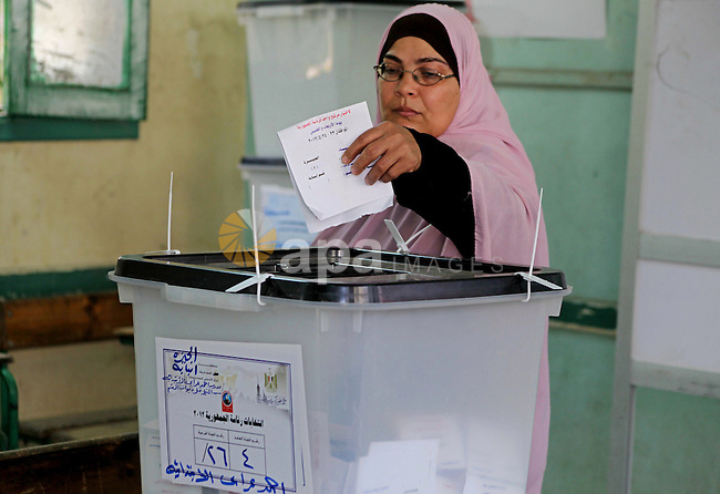 An Egyptian voter casts her ballots at one of the polling stations, on the first day of the presidential elections  in Cairo, Egypt, 23 May 2012. Egyptian voters, on 23 May, queued at polling stations for the first Presidential election since the ouster of former president Hosni Mubarak in February 2011. The first round vote is on . Photo by Ashraf Amra