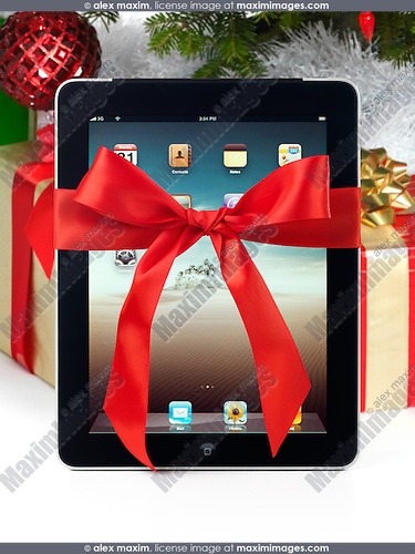 apple ipad 3g tablet with a red gift bow tied around it standing under a christmas