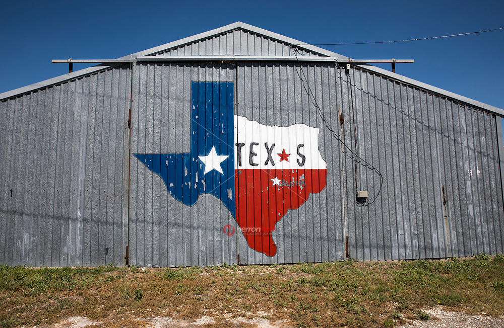 A painted State of Texas Lonestar outline painted on a barn symbolizing the State of Texas.
