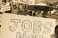 "Cov starts marching from the Occupy Orange County, Irvine camp on Saturday November 5 while a number of protesters hold signs in the background.   Her sign reads ""Jobs not cuts""."