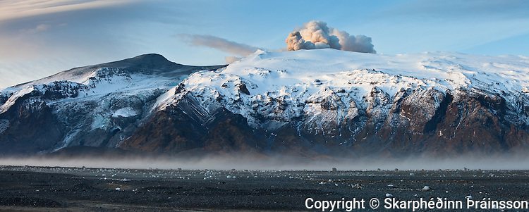 A panorama view of Eyjafjallaj&ouml;kull erupting volcano in south Iceland 2010. <br /> View from Flj&oacute;tshl&iacute;&eth; at sunrise. Stranded icecubes in foreground after a flod in Markarflj&oacute;t