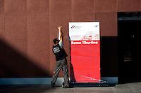 Roma 28 Novembre 2011.Inaugurata la nuova Stazione Tiburtina dell'alta velocità..Operaio  incarta  l'insegna Roma Tiburtina al termine dell'inaugurazione