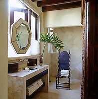 A guest bathroom has wall, floors and vanity unit of limestone and is furnished with an antique Portuguese leather chair