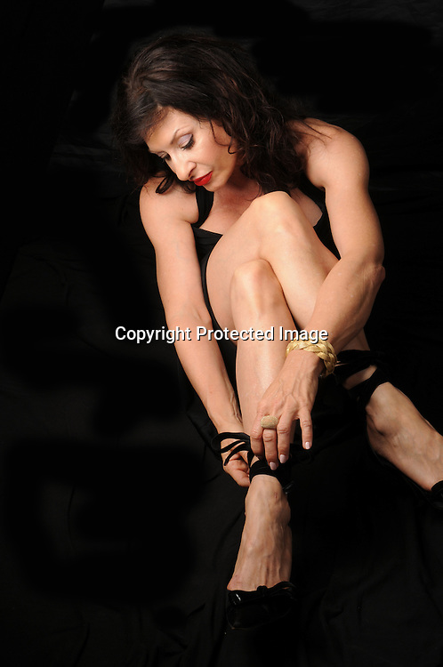 Mature woman tying her shoes stock photo