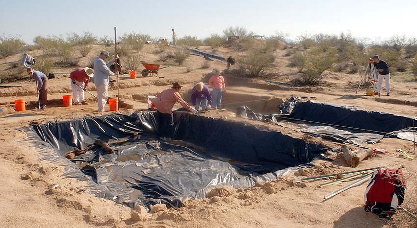 .University of arizona .students shovels dirt to be screened of dirt from.the Marana Platform mound looking for.shards and other artifacts from the .mound occupied for 100 years by the HoHoKam.people from 1200 ad to 1300 ad.....in this picture the students are evacuating.a room 40x40 in size, they have divided it up into.four sections and are working one quarter at a time...