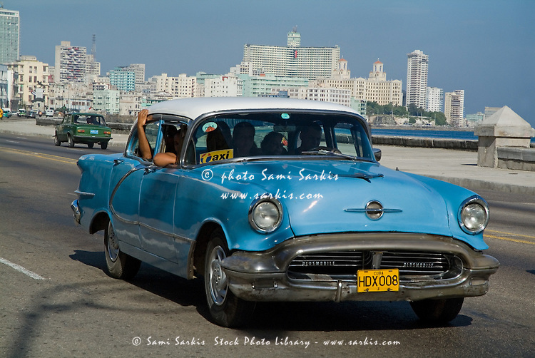 Classic American car used as a taxi driving in Malecon, Havana, Cuba