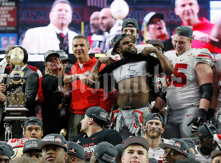 Ohio State Buckeyes running back Ezekiel Elliott (15) shows off his abs on the trophy podium following Ohio State's 44-28 win over the Notre Dame Fighting Irish in the Battlefrog Fiesta Bowl at University of Phoenix Stadium in Glendale, Arizona on Jan. 1, 2016. (Adam Cairns / The Columbus Dispatch)