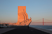 Padrao dos Descobrimentos or Monument to the Discoveries, and the 25 de Abril suspension bridge crossing the Tagus river estuary, Santa Maria de Belem, Lisbon, Portugal. The monument was built 1958-60, replacing an earlier monument built for the 1940 Portuguese World Fair, to celebrate the golden age of Portuguese exploration. The monument opened on the 5th centennial of the death of Henry the Navigator and features 33 statues of figures from the exploration age. Picture by Manuel Cohen