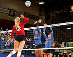 BROOKINGS, SD - SEPTEMBER 25:  Elizabeth Loschen #12 from the University of South Dakota looks to get a kill past Mikala Hora #14 and Nazya Thies #6 from South Dakota State University during their match Sunday afternoon at Frost Arena. (Photo by Dave Eggen/Inertia)